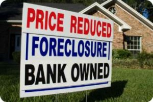 Price reduced bank owned foreclosure sign in front of home